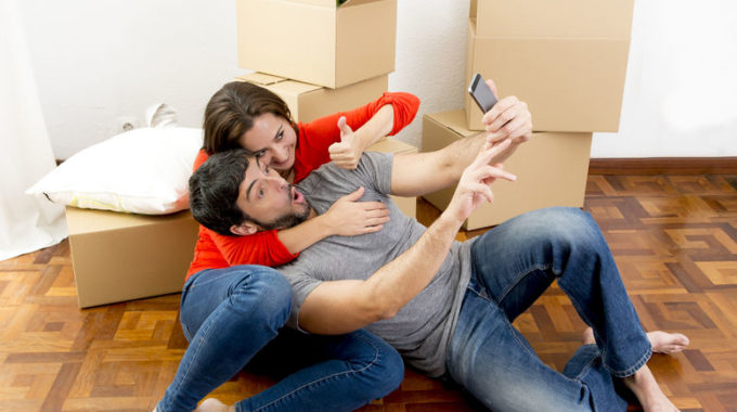 33097479 - Young Happy Couple Moving Together In A New House , Flat Or Apartment Unpacking Cardboard Boxes Home Belongings Having Fun Taking Selfie Video And Picture