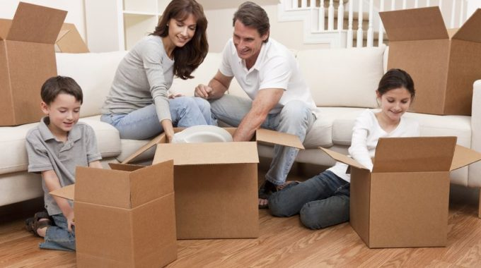 10549574 - Family, Parents, Son And Daughter, Unpacking Boxes And Moving Into A New Home.