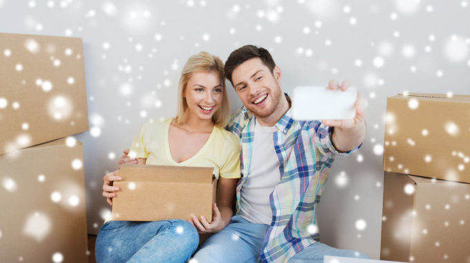 66158350 - Home, People, Technology And Real Estate Concept - Smiling Couple With Cardboard Boxes Moving To New Place And Taking Smartphone Selfie Over Snow