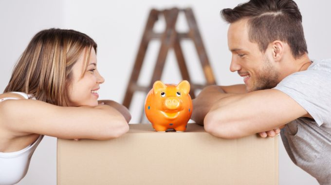 21162039 - New Happy Couple Looking At The Piggybank In A Savings Concept